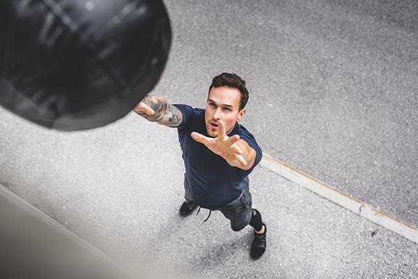 Man doing medicine ball squat and toss