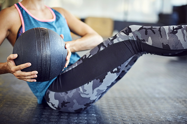 Woman doing Russian Twist a with medicine ball in gym.