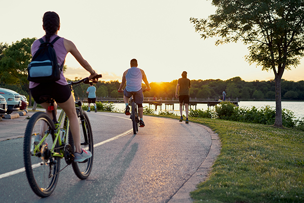 Bikers and runners on a trail at sunset.