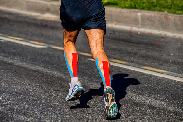 Cropped shot of runner's legs with KT Tape