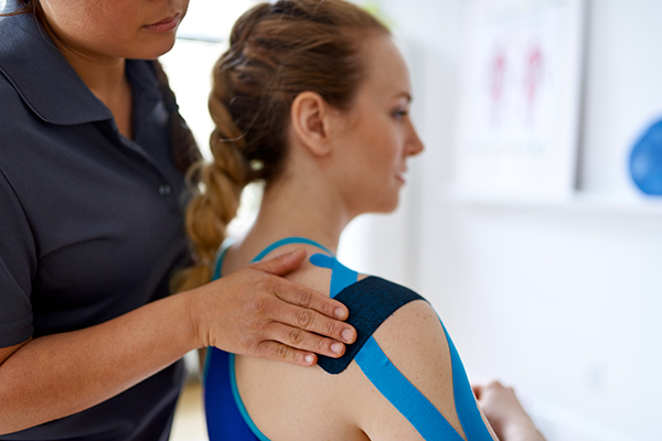 Woman apply KT tape to athlete's shoulder